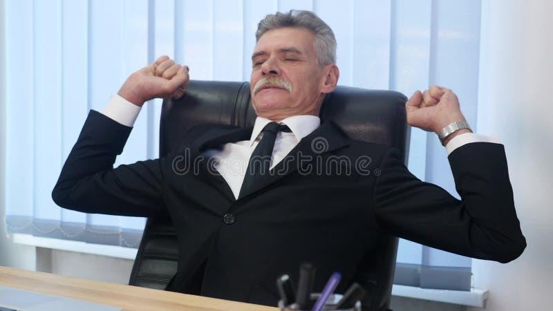 Oude die zakenman terug als zijn bureauvoorzitter wordt geleund, glimlacht hij en dagdromen royalty-vrije stock foto