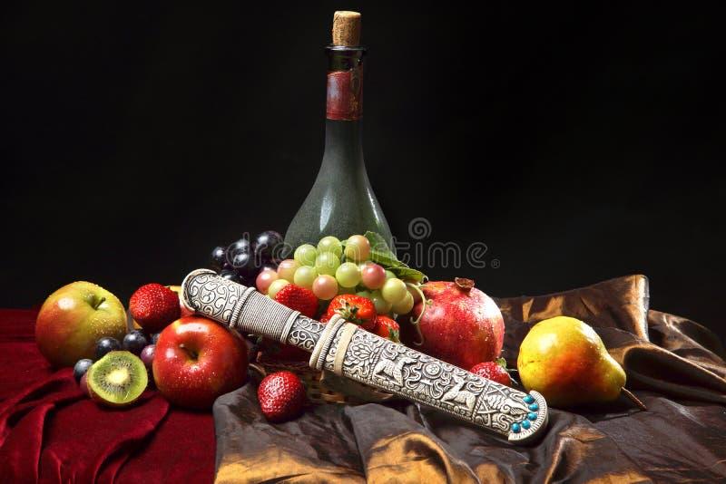 Oude dolk in de schede, klassiek Nederlands stilleven met stoffige horizontale fles wijn en vruchten op een donkerblauwe achtergr royalty-vrije stock afbeelding