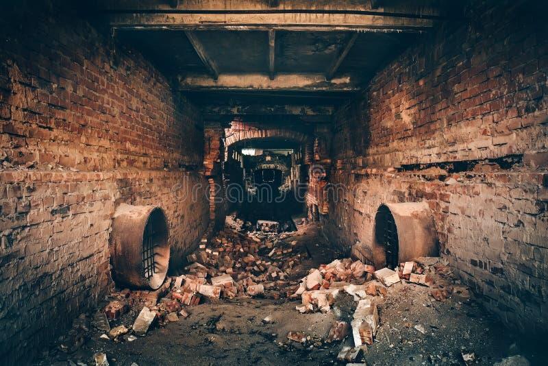 Oude donkere griezelige ondergrondse baksteentunnel of gang of rioolpijpleiding bij verlaten geruïneerde industriële fabriek stock afbeelding