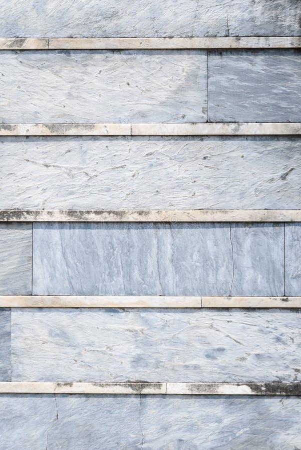 Oude doorstane blauwe grijze steenmuur met korstmos met horizontale lijnen, als geweven achtergrond stock foto's