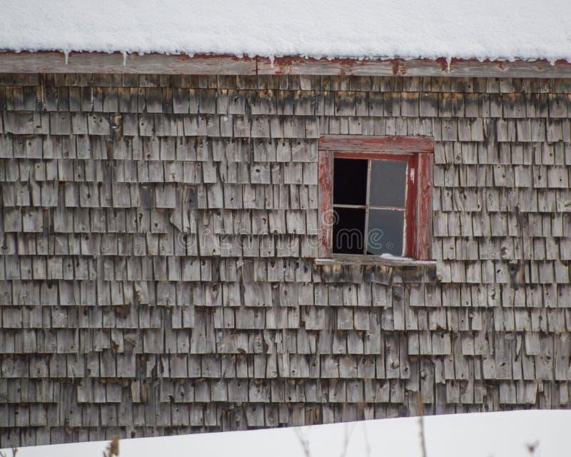 Oude doorstane de dakspanenschuur van cederschokken met de rode vensterwinter royalty-vrije stock afbeeldingen
