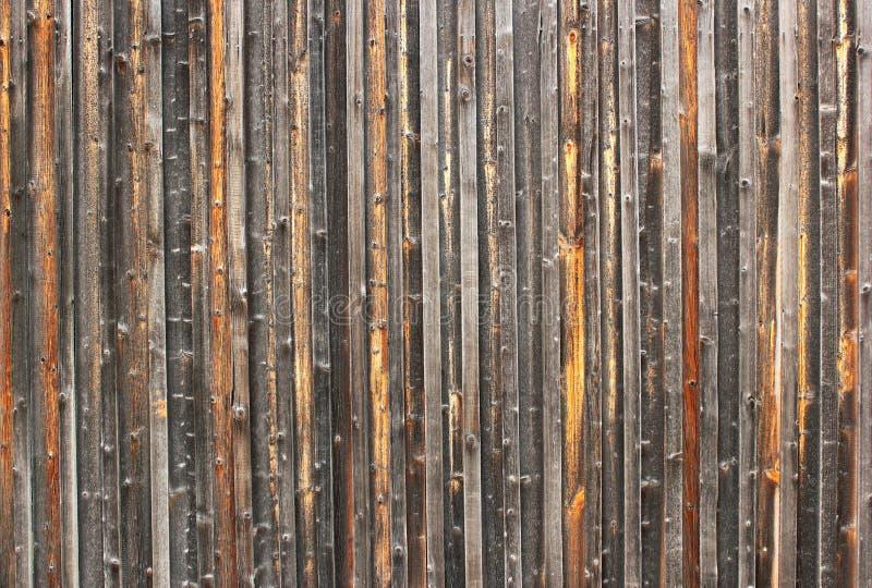 Oude doorstane die omheining van verticale houten planken wordt gemaakt stock afbeelding
