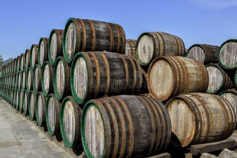 Oude doorstane houten in openlucht gestapelde wijnvatten stock fotografie