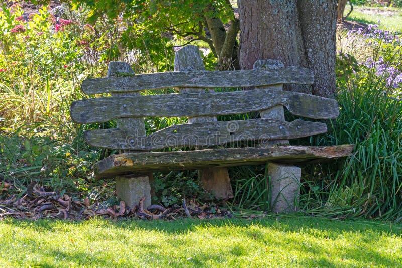 Oude doorstane houten parkbank stock fotografie