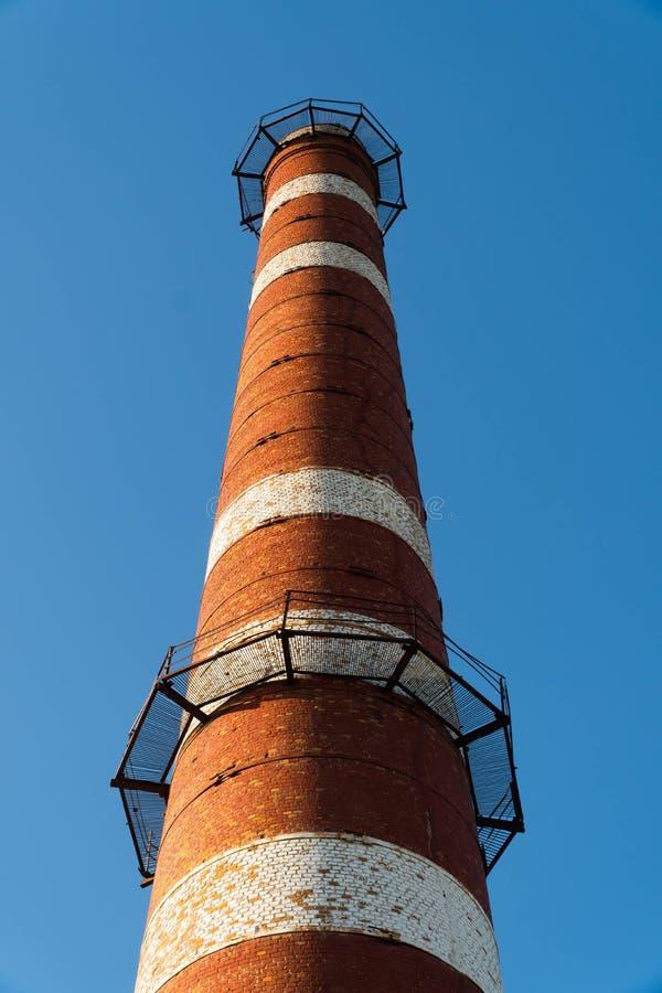 oude oude doorstane lange industriële fabrieksschoorsteen, de rode grungy wijnoogst van de baksteenschoorsteen grunge royalty-vrije stock fotografie