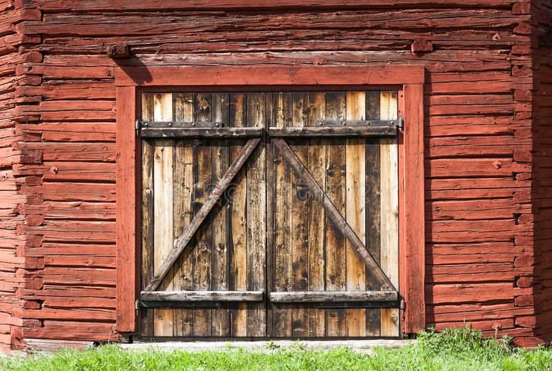 Oude doorstane staldeur op een historische die schuur met de beroemde rode verf van Falu wordt geschilderd stock afbeelding