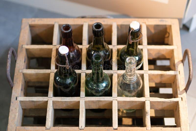Oude drankflessen in een houten geval Containers voor bier of citroen stock fotografie