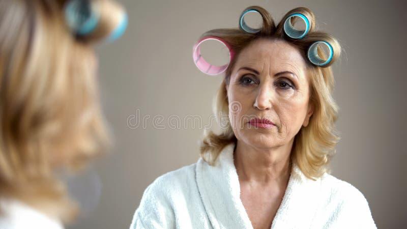 Oude droevige vrouw met haarkrulspelden en samenstelling die spiegelbezinning bekijken stock fotografie