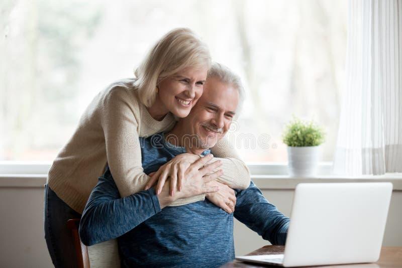 Oude echtgenoten die op grappige video's letten die computer met behulp van stock afbeelding