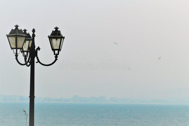 Oude eenzame lantaarn op de straat dichtbij het overzees royalty-vrije stock afbeelding