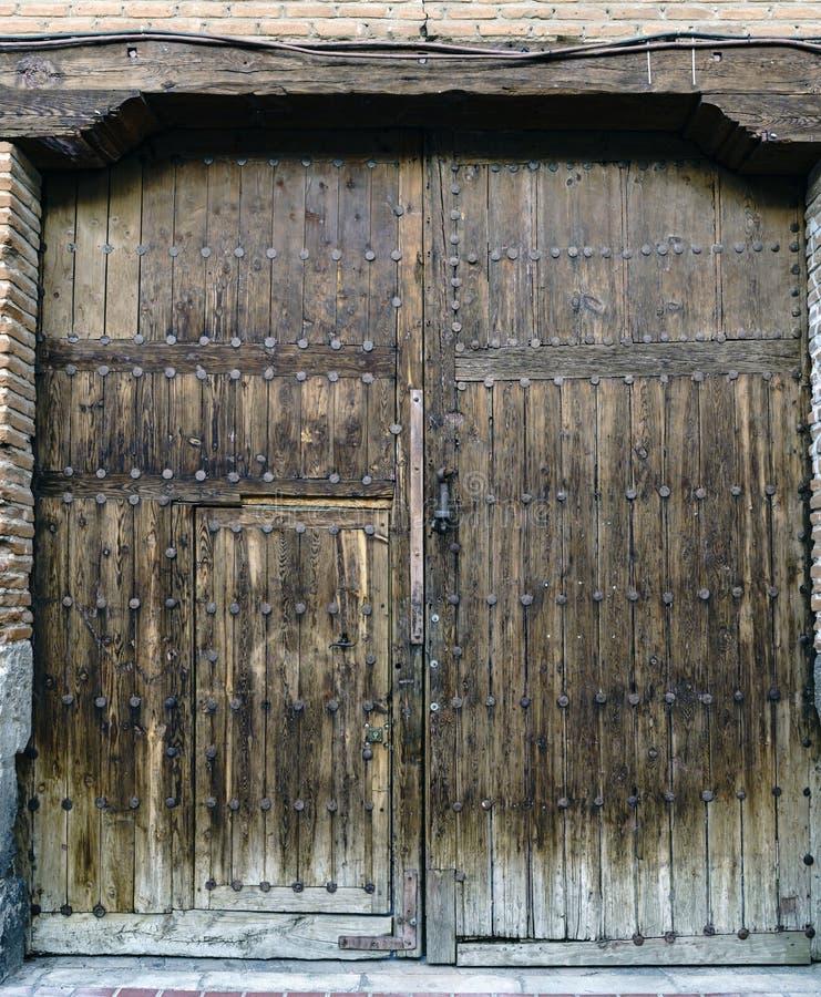 Oude eiken houtdeur met versterkingsspijkers, kleine deur en ijzerkloppers, met een houten straal op bovenkant Het diende voor de royalty-vrije stock afbeeldingen