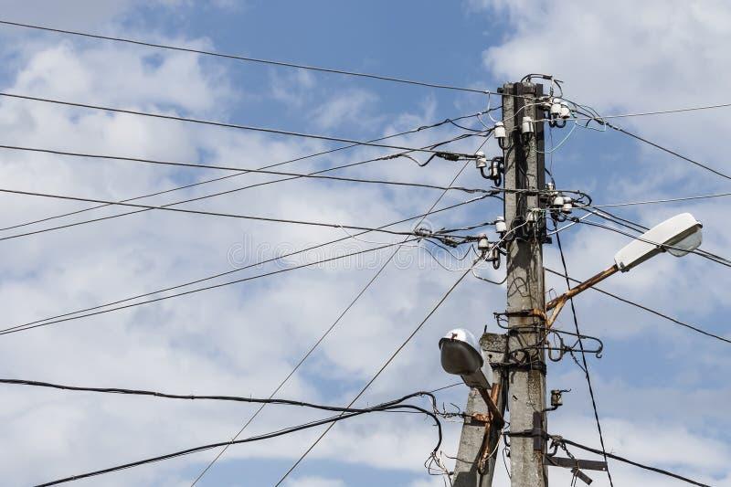 Oude elektrische straatpost met draden op hemelachtergrond stock fotografie