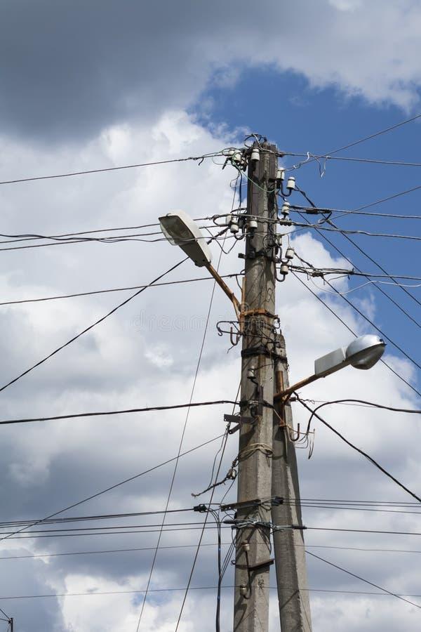 Oude elektrische straatpost met draden op hemelachtergrond stock afbeeldingen
