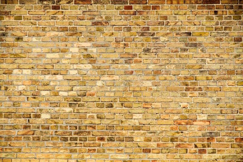 Oude en doorstane grungy gele en rode bakstenen muur als naadloze achtergrond van de patroontextuur royalty-vrije stock afbeeldingen