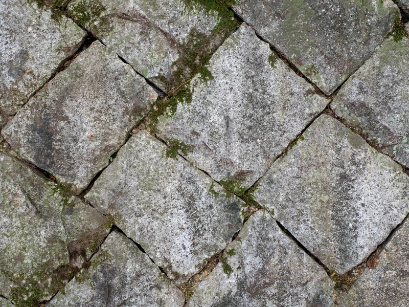 Oude en geregelde steenblokken met mos en grond in hiaten tussen royalty-vrije stock afbeelding