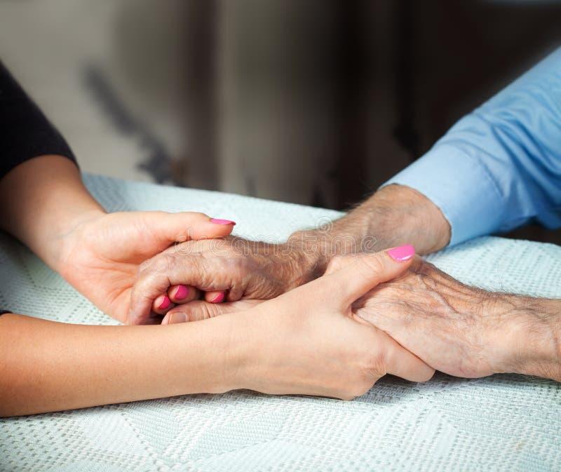 Oude en jonge holdingshanden op lichte achtergrond, close-up De zorg is thuis van bejaarden stock afbeeldingen