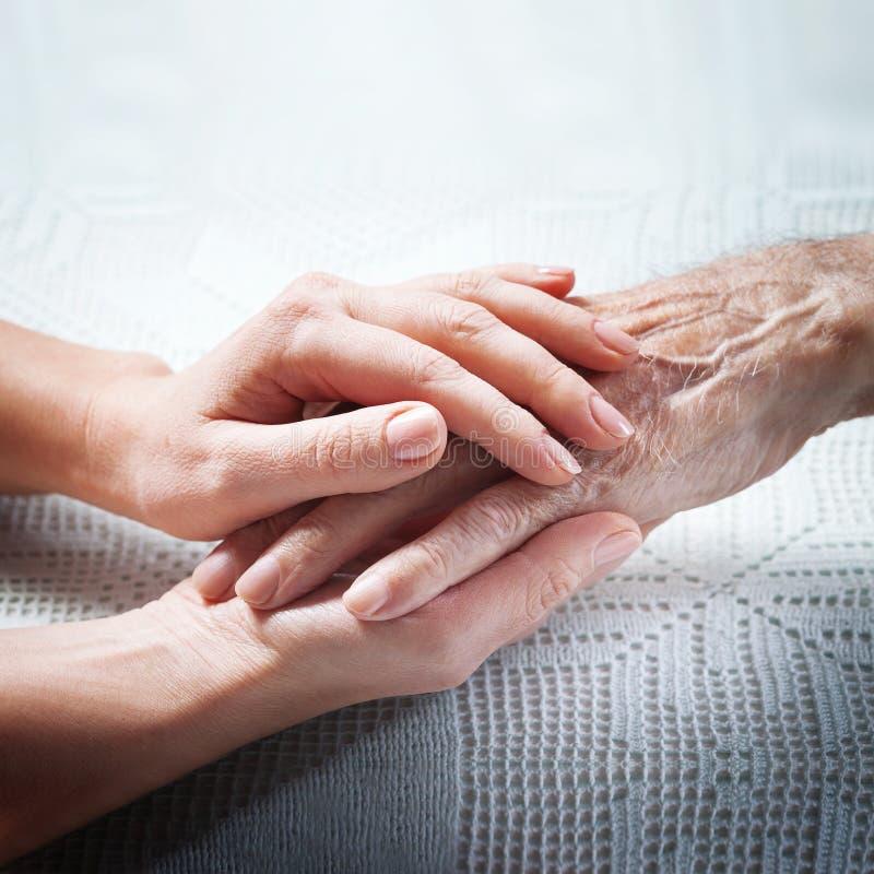 Oude en jonge holdingshanden op lichte achtergrond, close-up De zorg is thuis van bejaarden stock fotografie