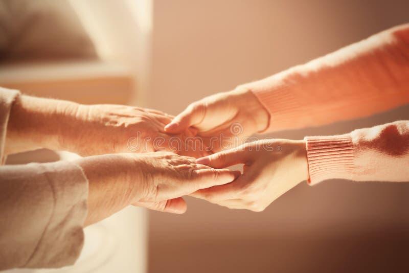 Oude en jonge vrouwen die handen op vage achtergrond houden stock foto