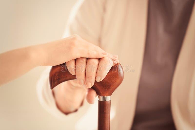 Oude en jonge vrouwen die handen op wandelstok houden royalty-vrije stock afbeeldingen