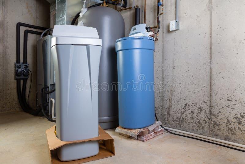 Oude en nieuwe wateronthardertanks in een nutsruimte stock foto
