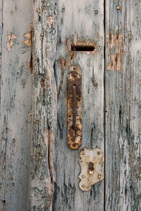 Oude en roestige deurknop met sleutelgat op bleke en uitstekende blauwe houten deuren royalty-vrije stock afbeeldingen