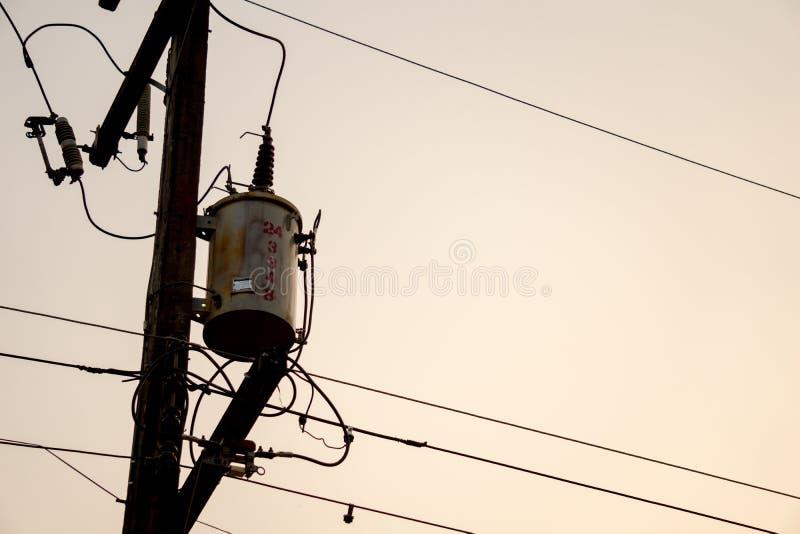 Oude en uitstekende elektrische transformator op elektriciteitspost met elektriciteitsdraden royalty-vrije stock fotografie