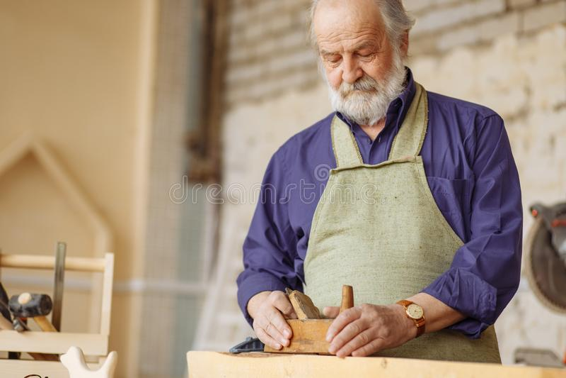 Oude ervaren timmerman die met houten planer aan plankworkshop werken stock afbeelding