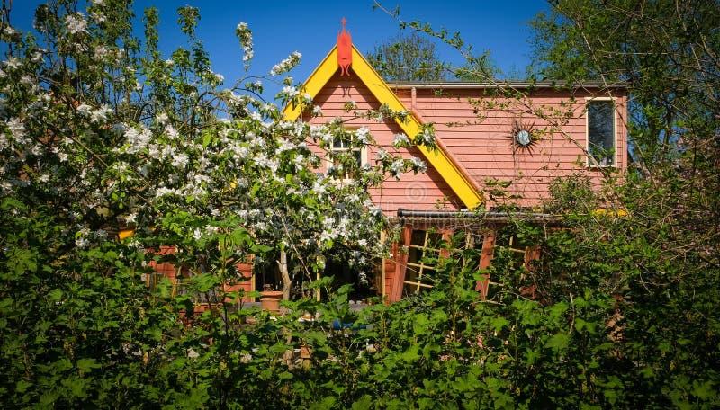 Oude Fashioned, houten huisdeur, huis ingang verborgen achter bomen stock afbeelding