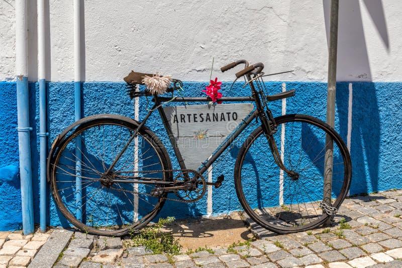 Oude fiets met de reclame van teken, Mertola, Portugal stock afbeelding