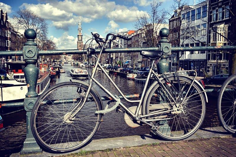 Oude fiets op brug. Cityscape van Amsterdam stock fotografie