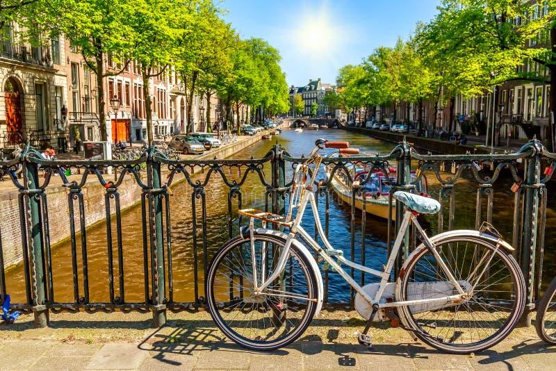 Oude fiets op de brug in Amsterdam, Nederland tegen een kanaal tijdens de zomer zonnige dag De prentbriefkaar iconische mening va stock afbeelding