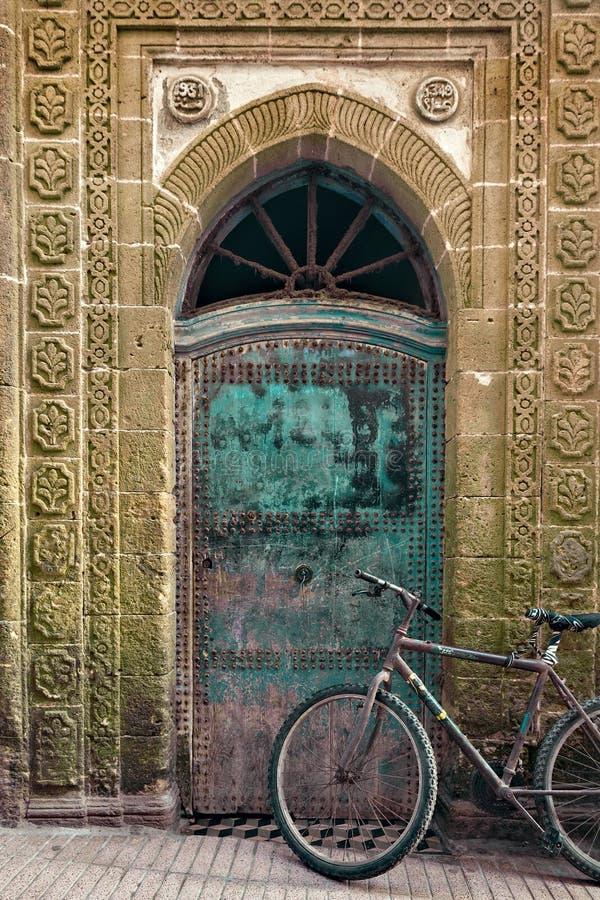 Oude fiets voor een doorstane deur, Marokko stock foto's
