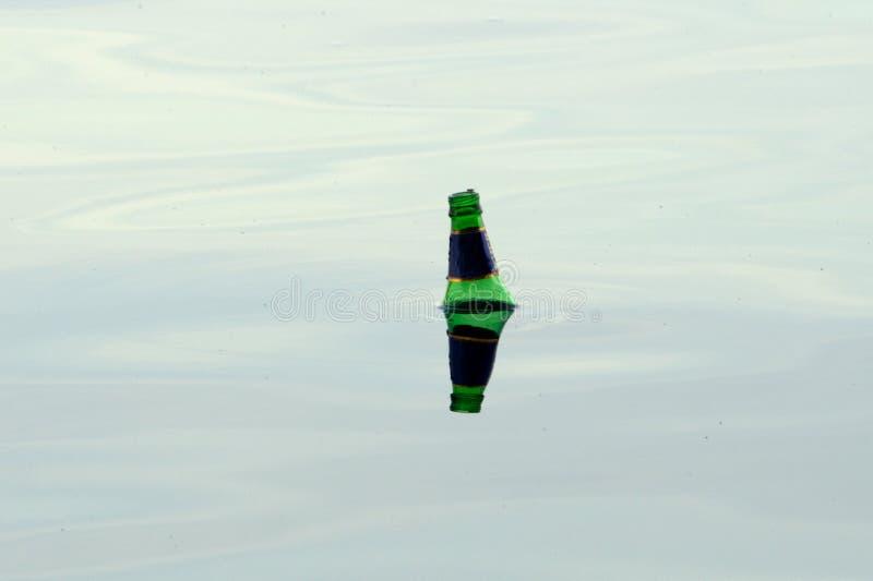 Oude flessen die in de water ruimtegifstof drijven royalty-vrije stock afbeeldingen