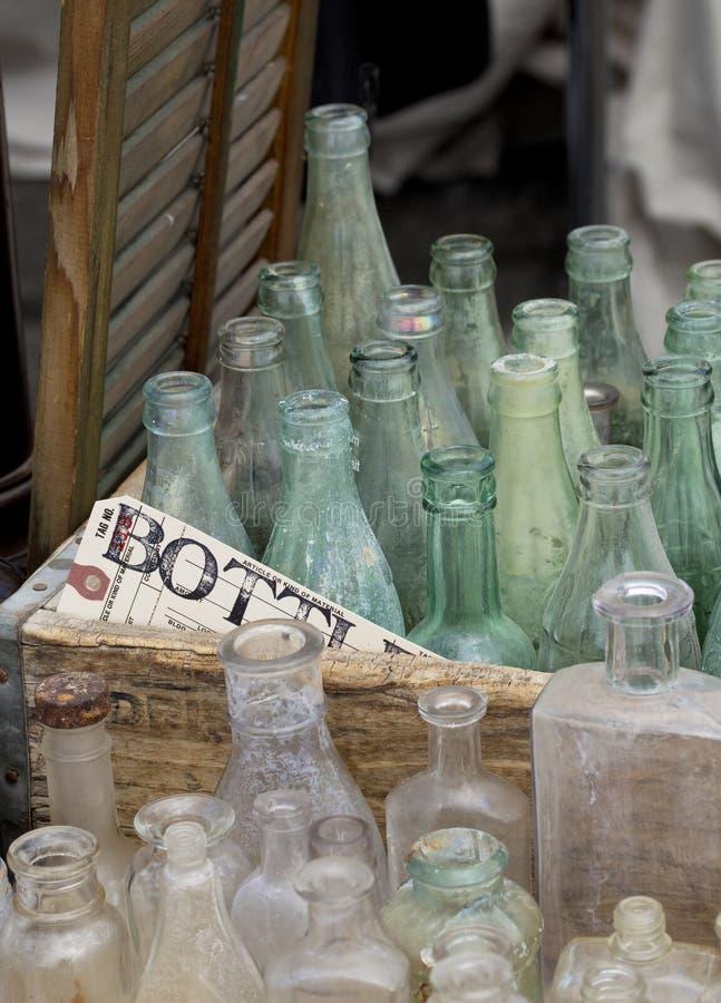 Oude flessen in krat stock foto