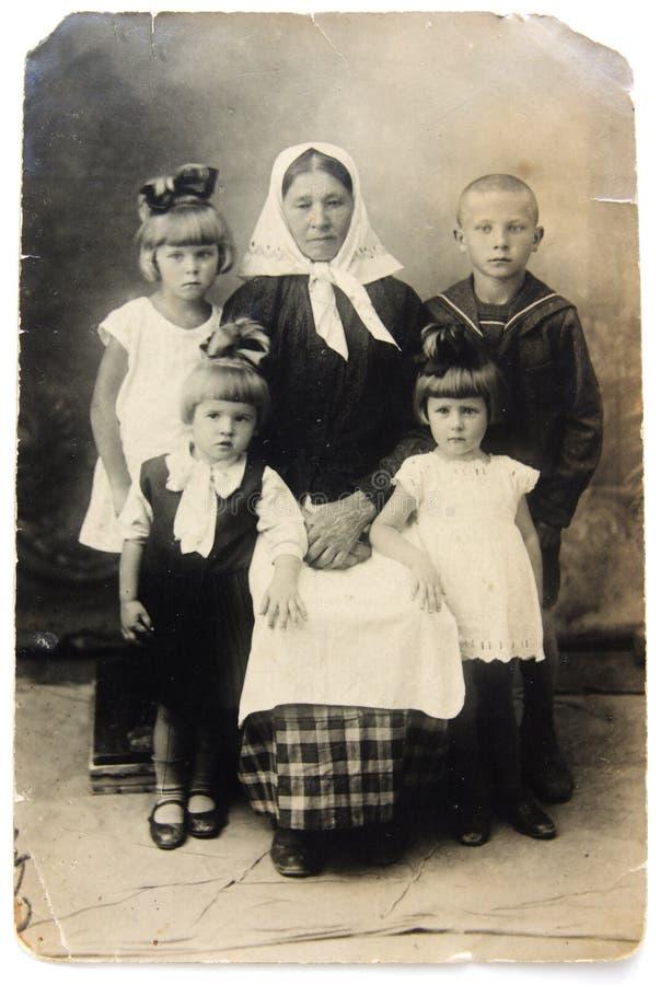 Oude foto van grootmoeder met kinderen stock foto