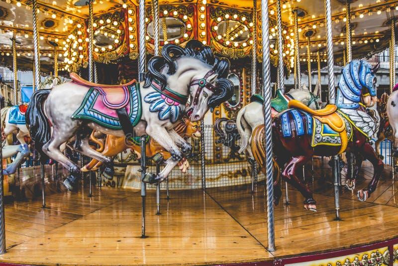 Oude Franse carrousel in een vakantiepark Drie paarden en vliegtuig stock afbeeldingen
