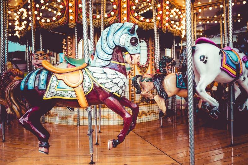 Oude Franse carrousel in een vakantiepark Drie paarden en vliegtuig op een traditionele kermisterrein uitstekende carrousel Vroli royalty-vrije stock afbeeldingen