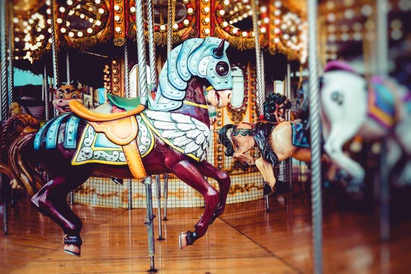Oude Franse carrousel in een vakantiepark Drie paarden en vliegtuig op een traditionele kermisterrein uitstekende carrousel Vroli royalty-vrije stock afbeelding