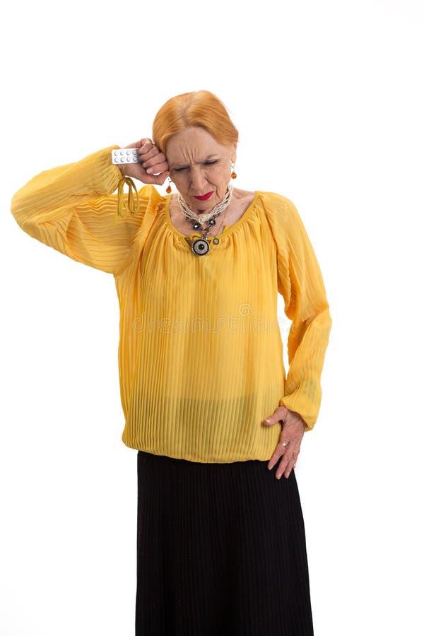 Oude geïsoleerde vrouw met pillen stock afbeelding