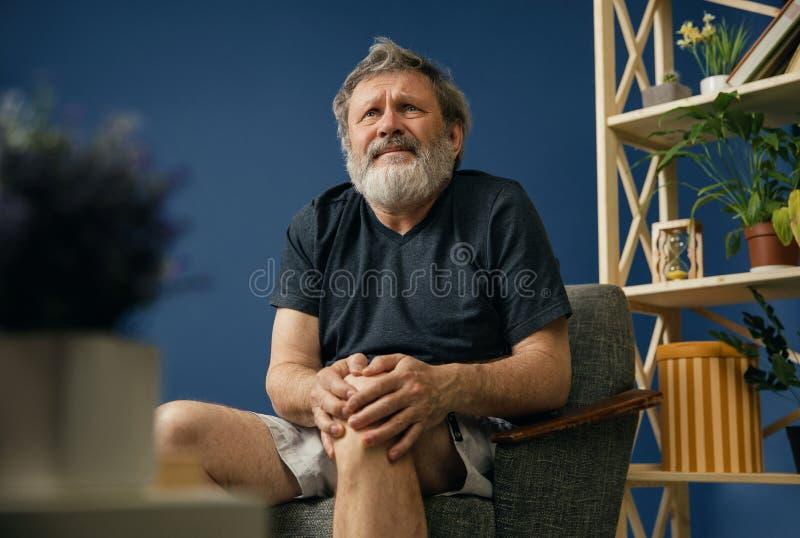 Oude gebaarde mens die aan kniepijn lijden stock afbeeldingen