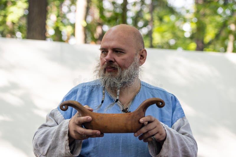 Oude gebaarde mens in oude klerendranken van een kom in de vorm van drakkar royalty-vrije stock fotografie