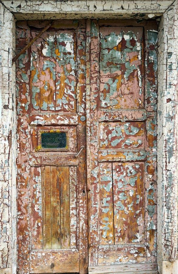 Oude gebarsten bruine deur op de voorzijde van het huis stock foto