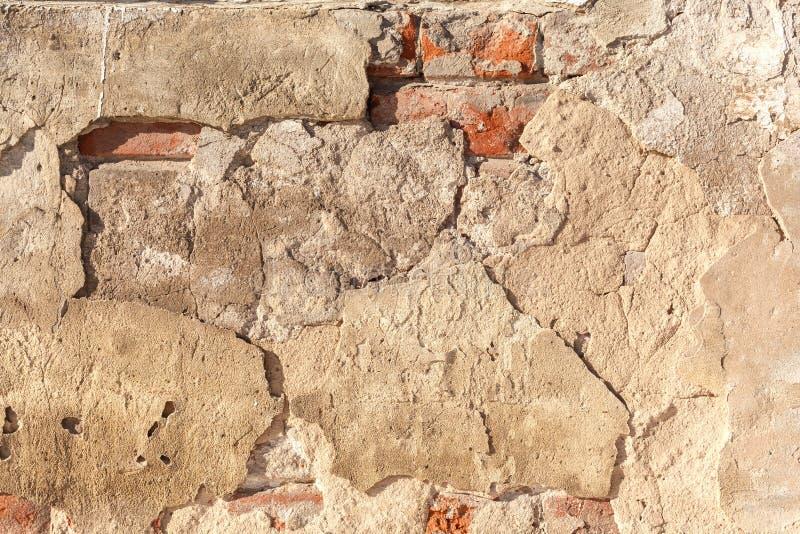 Oude gebarsten en geruïneerde die muur van rode bakstenen met overblijfselen van pleister wordt gemaakt Grunge Achtergrondgipsple stock fotografie