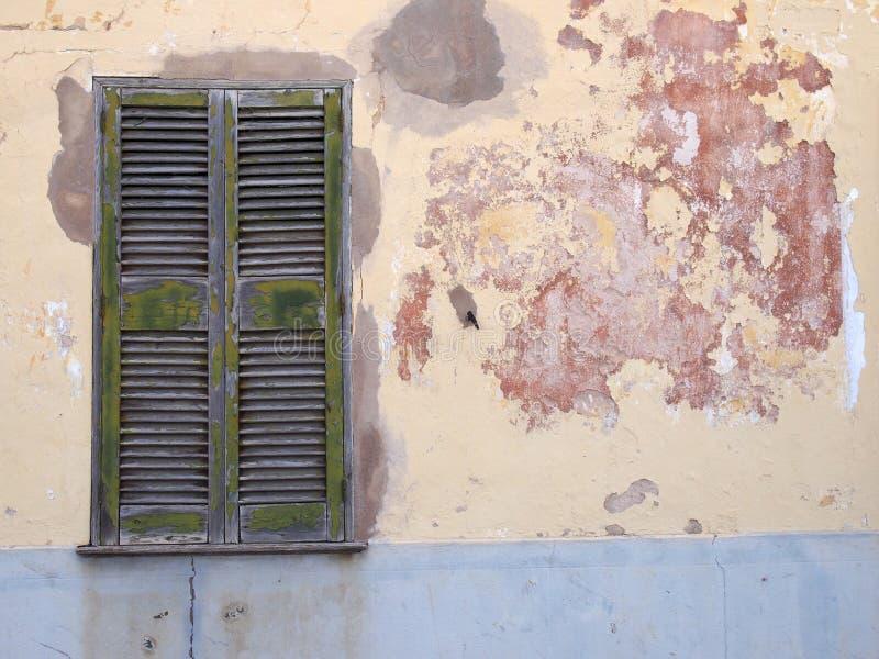Oude gebarsten huismuur met hersteld die cement in het afschilferen schillagen wordt geschilderd van grijze gele en rode verf met royalty-vrije stock afbeeldingen