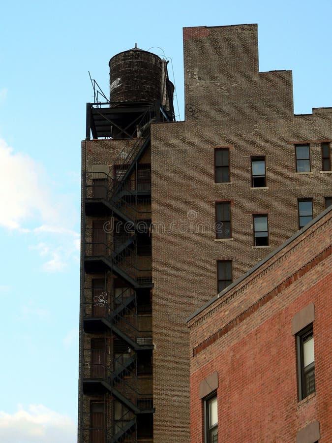 Oude gebouwen in de Stad van New York tegen een heldere hemel stock fotografie