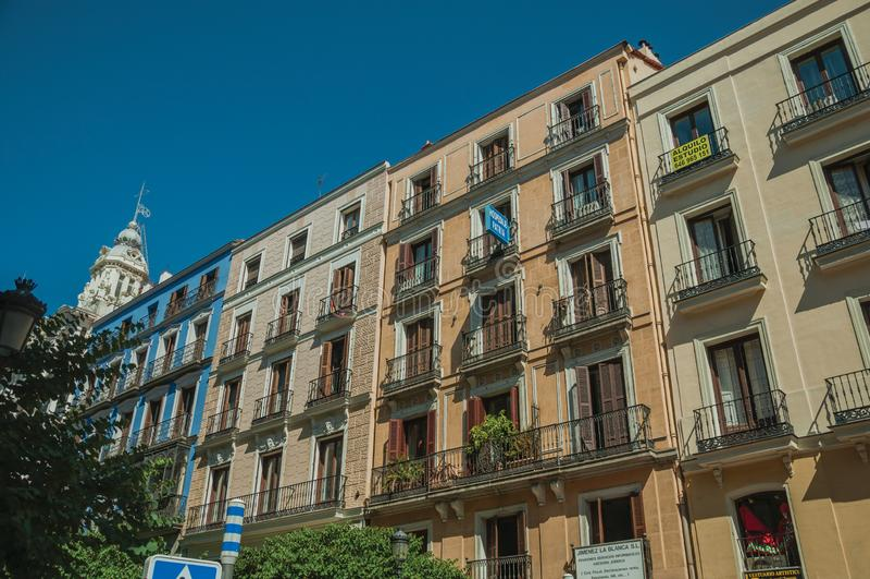 Oude gebouwen met voorgevelhoogtepunt van vensters en balkons in Madrid stock afbeelding