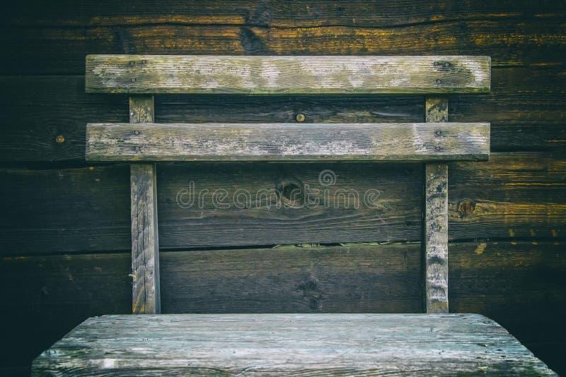 Oude gebrande raad met spijkers in bruine en zwarte kleur als achtergrond een houten stoeltribunes vóór dat stock foto