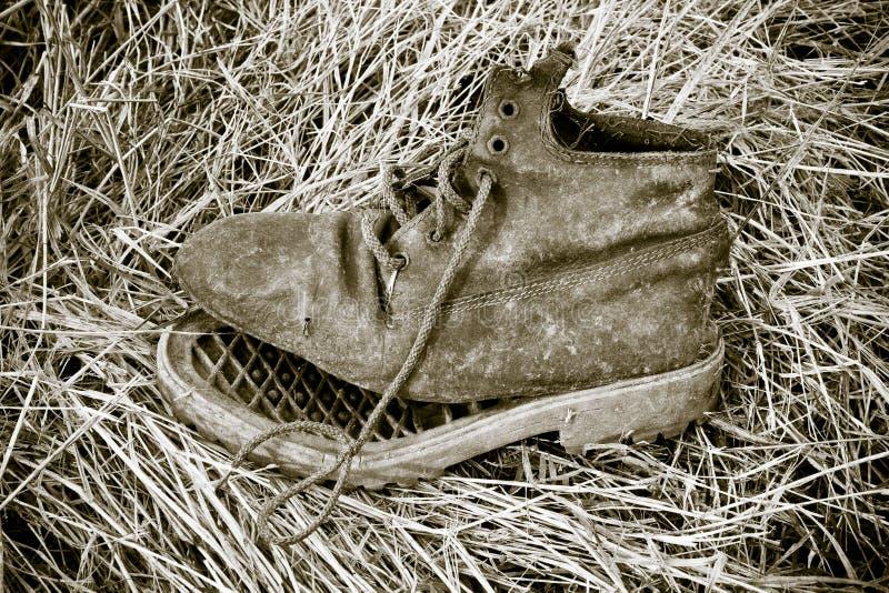 Oude gebroken die laars in een droog grastapijt wordt verlaten - armoedeconce stock foto's