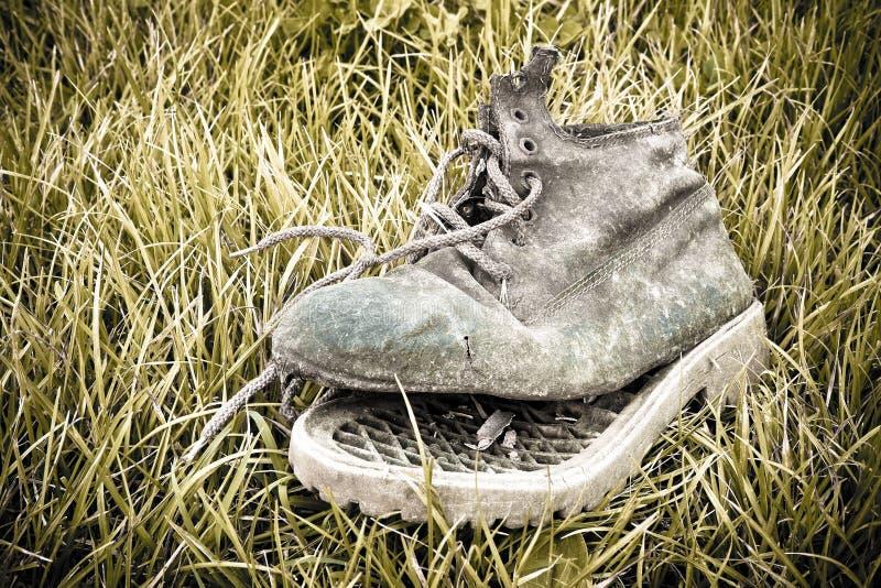Oude gebroken die laars in een grastapijt wordt verlaten royalty-vrije stock fotografie