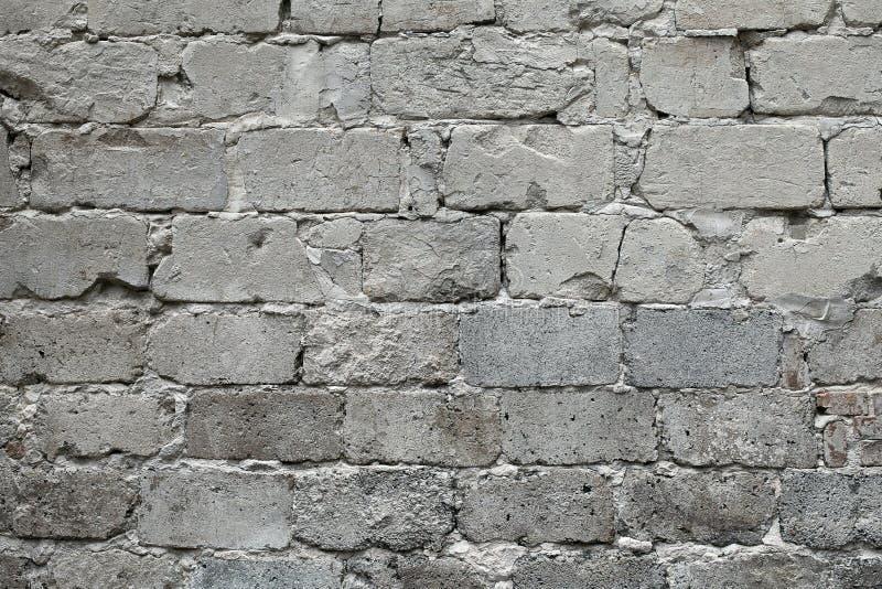 Oude gebroken grijze bakstenen muurachtergrond Oude grijze beschadigde bakstenen muurtextuur, Grijze baksteenachtergrond en textu stock foto